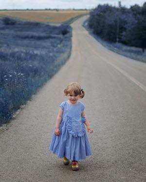 Felicia Simion Girl in purple dress walking on road by meadow