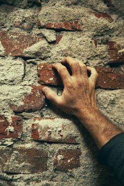 Kerstin Marinov Man's hand holding brick in wall