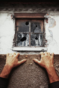 Kerstin Marinov Hands of man hanging from wall by window of abandoned building