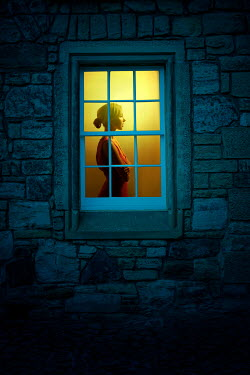 Miguel Sobreira Woman standing in illuminated window
