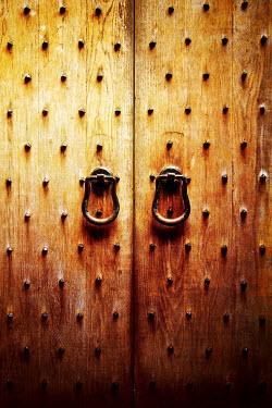 Miguel Sobreira Studded wooden door with metal handles