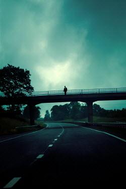 Miguel Sobreira Man in suit standing on bridge over highway