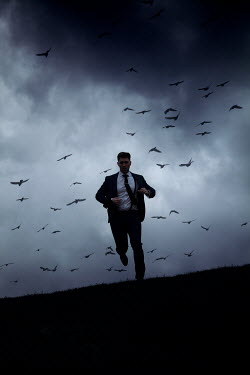 Miguel Sobreira Man in suit running on hill with birds