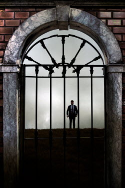 Miguel Sobreira Man in suit walking on hill through gate