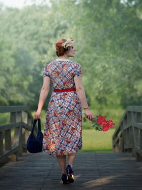 Elisabeth Ansley Young woman in 1920s dress walking on bridge