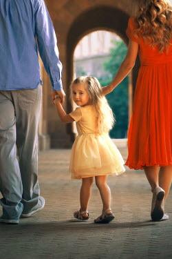 ILINA SIMEONOVA Family holding hands while walking under portico
