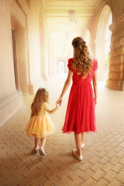ILINA SIMEONOVA Mother and daughter holding hands while walking under portico