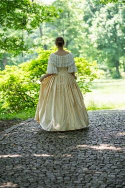 Jaroslaw Blaminsky Young woman in yellow dress walking on cobblestone path