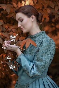 Jaroslaw Blaminsky Young woman in regency dress holding branch of autumn tree