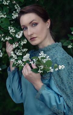 Jaroslaw Blaminsky Young woman in regency dress holding branch of tree with flowers