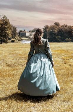 Jaroslaw Blaminsky Young woman in regency dress walking in field