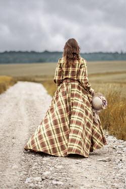 Jaroslaw Blaminsky Young woman in checked dress walking on rural road
