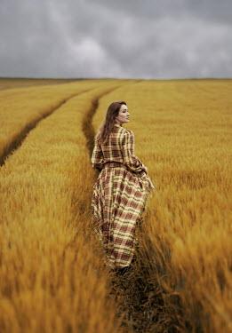 Jaroslaw Blaminsky Young woman in checked dress walking in field
