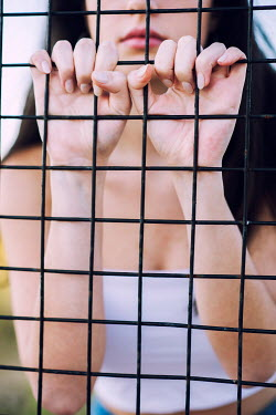 Mohamad Itani Young woman behind fence