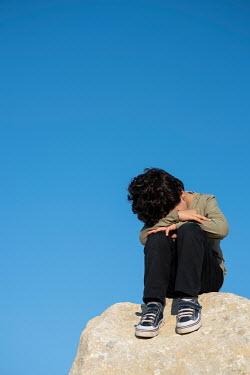 Mohamad Itani Crying boy sitting on rock