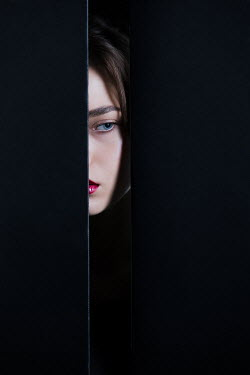 Magdalena Russocka woman peeking out through gap in wall