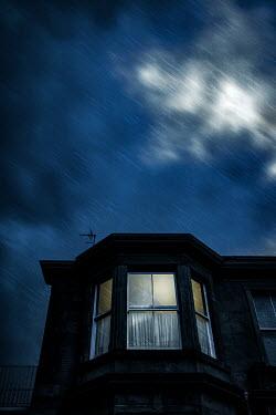 Natasza Fiedotjew light in attic window in town house on rainy night