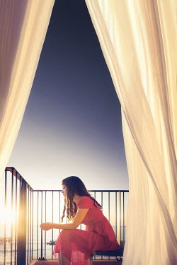 ILINA SIMEONOVA Young woman in red dress sitting on balcony chair at sunset