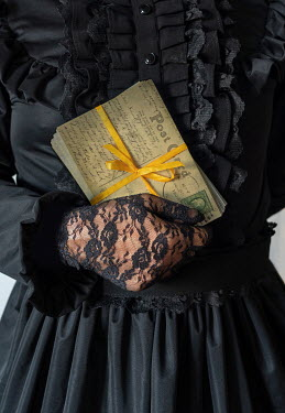 Jaroslaw Blaminsky Hands of woman with lace gloves holding postcards