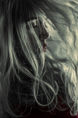 Magdalena Russocka close up of blonde woman with blown hair in shadowy room