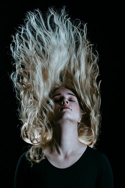 Magdalena Russocka blonde woman with blown up hair in shadowy room