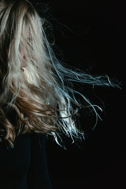 Magdalena Russocka blonde woman with blown hair in shadowy room