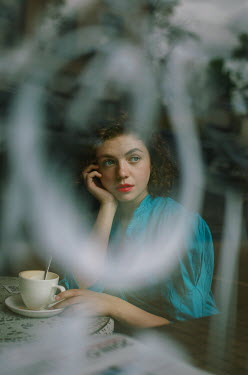 Svitozar Bilorusov Young woman sitting at table behind window in cafe
