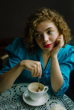 Svitozar Bilorusov Young woman with coffee at cafe table