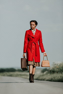 Magdalena Russocka retro african woman carrying suitcase walking on country road