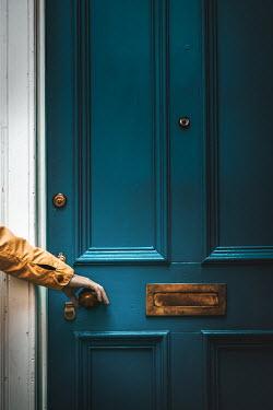 Natasza Fiedotjew male hand in yellow jacket holding door knob