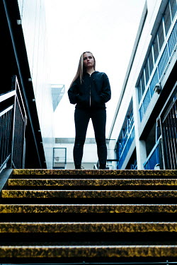 Shelley Richmond Young woman in black hoodie standing on staircase in city