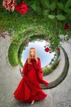 ILINA SIMEONOVA Young woman in red dress standing in little world garden