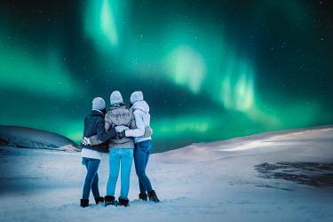 Evelina Kremsdorf Women standing in snow under aurora borealis in Iceland