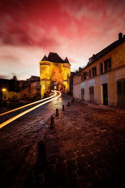 David Keochkerian Light trail of car driving under medieval gate