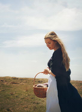 Mark Owen Young woman with basket in field