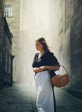 Mark Owen Woman with apron and basket on city street
