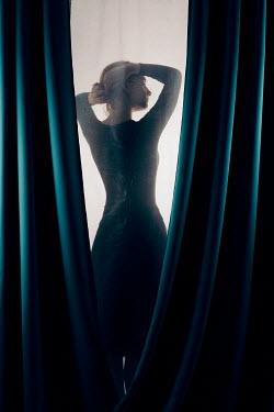 Magdalena Russocka woman combing hair standing behind curtains