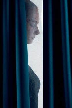 Magdalena Russocka woman standing behind curtains