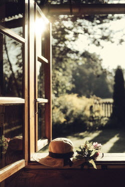 Magdalena Russocka hat and bunch of flowers in open cottage window