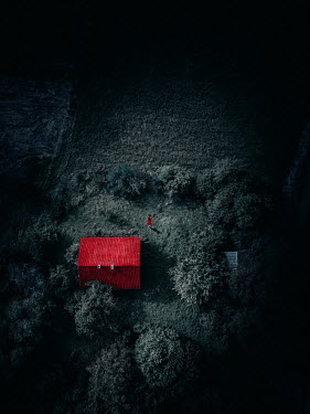 Magdalena Russocka woman in red dress walking by old cottage house from above