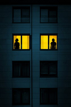 Magdalena Russocka silhouettes of two women in illuminated windows of modern apartment block at night