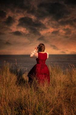 Nic Skerten HISTORICAL WOMAN WATCHING SEA AT SUNSET
