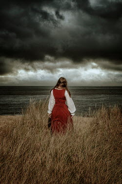 Nic Skerten HISTORICAL WOMAN WATCHING SEA WITH STORMY SKY