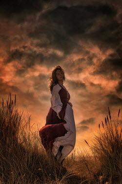 Nic Skerten HISTORICAL WOMAN IN WINDY SAND DUNES AT SUNSET