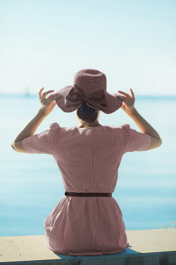 Ildiko Neer Young woman holding hat by sea