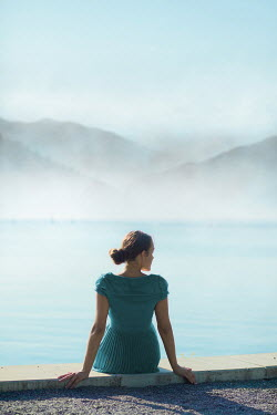 Ildiko Neer Young woman sitting by lake