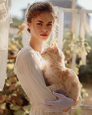 Georgy Chernyadyev WOMAN HOLDING CAT IN SUNLIT GARDEN