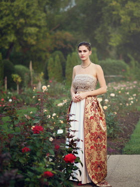 Elisabeth Ansley GIRL WITH SLEEVELESS GOWN STANDING  IN ROSE GARDEN