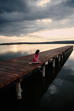 Nikaa WOMAN IN RED SITTING ON JETTY BY WATER