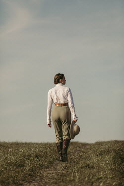 Magdalena Russocka young woman wearing safari outfit walking in field